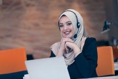 Mujer árabe del operador hermoso del teléfono que trabaja en oficina de lanzamiento imagenes de archivo