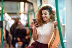 Mujer ?rabe dentro del metro que mira su smartphone fotos de archivo libres de regalías