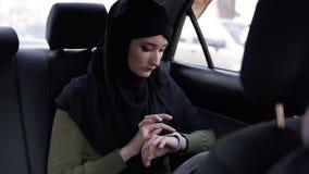 Mujer árabe en el hijab negro que se sienta en el asiento trasero en el coche y que usa sus relojes elegantes, golpe fuerte los d almacen de video