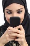 Mujer árabe enviciada al smartphone Fotos de archivo