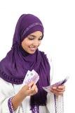 Mujer árabe hermosa que cuenta muchos quinientos billetes de banco de los euros Fotografía de archivo libre de regalías