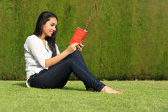 Mujer árabe hermosa que lee un libro que se sienta en el césped en el parque Imagen de archivo libre de regalías