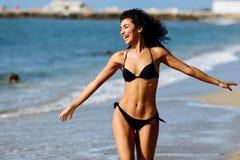 Mujer ?rabe joven con el cuerpo hermoso en traje de ba?o que sonr?e en una playa tropical foto de archivo