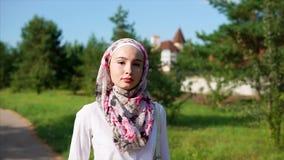 Mujer árabe joven que camina en el parque que lleva un hijab en una ciudad moderna metrajes