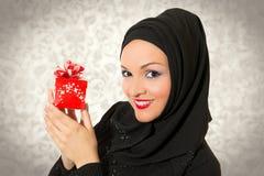 Mujer árabe, presente que se sostiene vestido tradicional Imagen de archivo