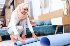 Mujer árabe que prepara una estera para hacer la gimnasia en el dormitorio imagenes de archivo