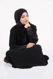 Mujer árabe que se sienta en el piso Foto de archivo