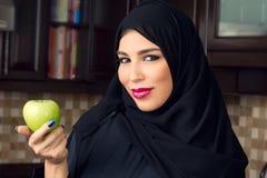 Mujer árabe que sostiene una manzana en la cocina Fotos de archivo