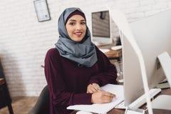 Mujer árabe que trabaja en oficina El trabajador de sexo femenino está tomando notas en la tabla foto de archivo