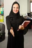 Mujer árabe, saludando a una persona dentro de la oficina Foto de archivo libre de regalías