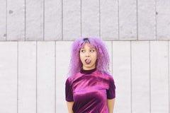 Mujer étnica con el pelo púrpura que sopla una goma rosada Fotografía de archivo