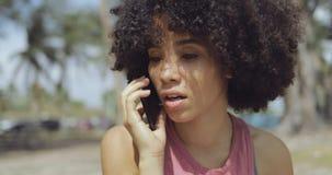 Mujer étnica contenta que habla en el teléfono metrajes