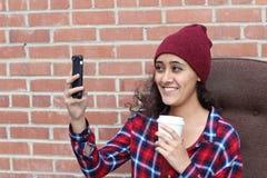 Mujer étnica joven que toma el selfie que sostiene una taza de café Imagenes de archivo