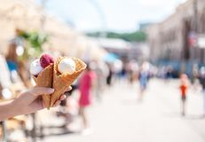Mujer \ 'mano de s que sostiene dos conos de la galleta con las bolas blancas y magentas del helado en el fondo alegre borroso de imagen de archivo libre de regalías