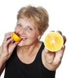 Mujer (67 años) que come la naranja Foto de archivo