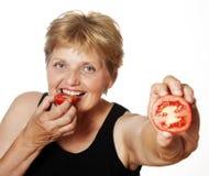 Mujer (67 años) que come un tomate Imágenes de archivo libres de regalías
