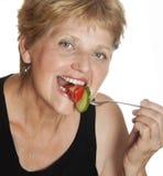 Mujer (67 años) que come vehículos Imágenes de archivo libres de regalías