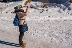 Mujer 50 años que toman una foto con el móvil en las montañas Imágenes de archivo libres de regalías