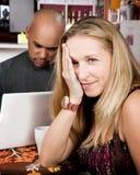 Mujer aburrida con el hombre en el ordenador portátil Imágenes de archivo libres de regalías