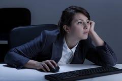 Mujer aburrida durante en horas extras Fotografía de archivo