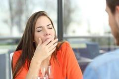 Mujer aburrida en una mala fecha imagen de archivo