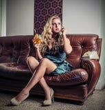Mujer aburrida hermosa que llama por teléfono a sentarse en el sofá Imágenes de archivo libres de regalías