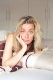 Mujer aburrida lindada a su cama Fotografía de archivo libre de regalías