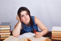 Mujer aburrida perezosa joven del estudiante que se sienta en la tabla con el texto BO Imagen de archivo