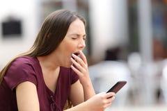 Mujer aburrida que bosteza con un teléfono móvil Imagen de archivo
