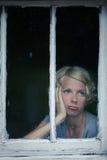 Mujer aburrida que mira el tiempo lluvioso por la ventana fotografía de archivo libre de regalías