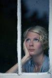 Mujer aburrida que mira el tiempo lluvioso por la ventana imágenes de archivo libres de regalías