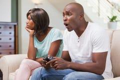 Mujer aburrida que se sienta al lado de su novio que juega a los videojuegos Imagen de archivo libre de regalías