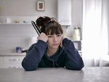 Mujer aburrida que se sienta con teledirigido en un fondo borroso de la cocina imagenes de archivo