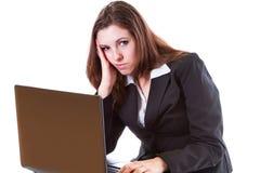 Mujer aburrida que trabaja en la computadora portátil Imagenes de archivo
