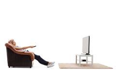 Mujer aburrida que ve la TV Imágenes de archivo libres de regalías