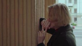 Mujer abusada que llora cerca de la pared al aire libre almacen de metraje de vídeo