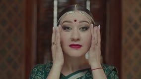 Mujer acabada del maquillaje en sari que se admira metrajes