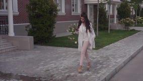 Mujer acertada atractiva joven que camina abajo de la calle usando su smartphone almacen de metraje de vídeo