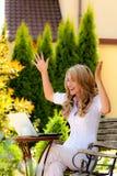 Mujer acertada con una computadora portátil en el jardín Fotografía de archivo