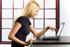 Mujer acertada en la computadora portátil Fotografía de archivo