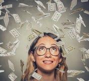 Mujer acertada feliz en los vidrios que miran para arriba debajo de una lluvia del dinero Fotografía de archivo