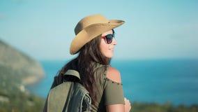 Mujer acertada sonriente del backpacker que admira paisaje marino que sorprende en el pico de la montaña almacen de metraje de vídeo