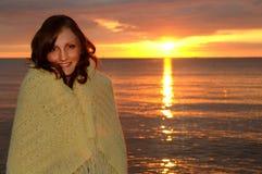 Mujer acogedora envuelta en manta en la puesta del sol Foto de archivo libre de regalías