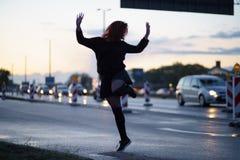 Mujer activa del bailarín del viajero que se realiza en un sitio de la construcción de carreteras en el tiempo de la puesta del s fotos de archivo libres de regalías