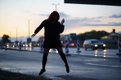 Mujer activa del bailar?n del viajero que se realiza en un sitio de la construcci?n de carreteras en el tiempo de la puesta del s fotos de archivo