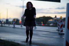 Mujer activa del bailar?n del viajero que se realiza en un sitio de la construcci?n de carreteras en el tiempo de la puesta del s imagenes de archivo