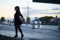 Mujer activa del bailar?n del viajero que se realiza en un sitio de la construcci?n de carreteras en el tiempo de la puesta del s fotografía de archivo libre de regalías