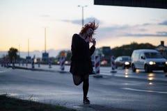 Mujer activa del bailar?n del viajero que se realiza en un sitio de la construcci?n de carreteras en el tiempo de la puesta del s imágenes de archivo libres de regalías