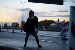 Mujer activa del bailar?n del viajero que se realiza en un sitio de la construcci?n de carreteras en el tiempo de la puesta del s foto de archivo