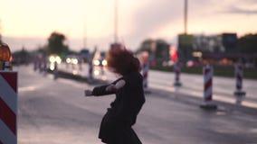 Mujer activa del bailar?n del viajero que se realiza en un sitio de la construcci?n de carreteras en el tiempo de la puesta del s almacen de metraje de vídeo